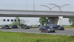 Cars on highway drive underneath a bridge Stock Footage