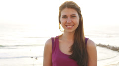 Handheld close up of pretty Caucasian girl smiling at camera on the beach - stock footage