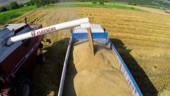Combine harvester unloading grain into the truck Stock Footage