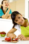 smiling happy woman cutting tomatoes for healthy food - stock photo