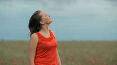 Beautiful Girl in red dress among poppy field looking on the sky Stock Footage