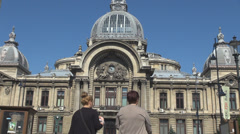 People walking in front of National Bank Palace Bucharest landmark summer season Stock Footage
