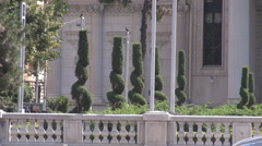 Nice garden in front of Bucharest Athenaeum, trees ornamented in spiral style Stock Footage