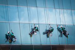 Group of workers cleaning windows service on high rise building Stock Photos