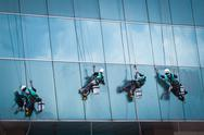 Stock Photo of group of workers cleaning windows service on high rise building