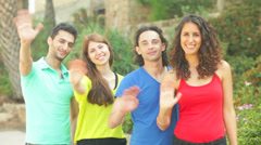 Four friends waving hands to camera for a snapshot Stock Footage
