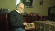 Stock Video Footage of 80 Years Old Man, Looking In An Photo Album, Memories, Family, Nostalgic
