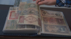 Money collection, numismatic bank-notes files hand browsing pages cultural hobby Stock Footage