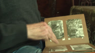 Stock Video Footage of 80 Years Old Man Hand Detail, Flipping Photo Album, Nostalgic, Arthritis, Tilt
