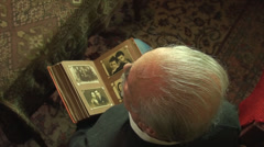Stock Video Footage of 80 Years Old Man, Looking In An Photo Album, Memories, Family, Above Shot Pan