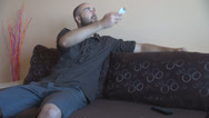 Stock Video Footage of Man using air conditioner remote controller for cooler air in room happy relaxed