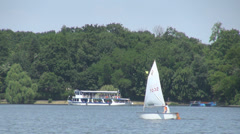 Sail boat passing near a transport vessel, forest background in summer sunny day Stock Footage