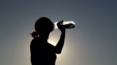 Young woman drink water at sunset.Girl drinks water from a bottle (banks) Stock Footage