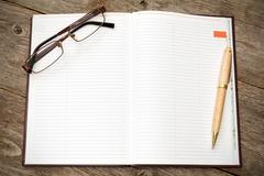Stock Photo of open notebook with pen and glasses