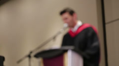 Out of focus male speaker on the podium during a graduation cermony - stock footage