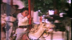 1098 - children on merry go round at amusement park - vintage film home movie Stock Footage
