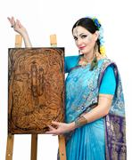 Stock Photo of artist standing at the easel with pyrography painting eternal harmony