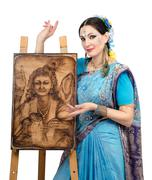 Stock Photo of artist showing pyrography painting prosperity on the easel