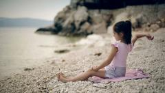 Child sits on the beach of the Adriatic Sea and throwing stones into the water. Stock Footage