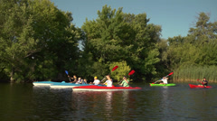Company of young people go kayaking on the river among reeds Stock Footage