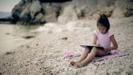 Stock Video Footage of A child sits on a stone near the Adriatic Sea and draws a picture. Medium shot.