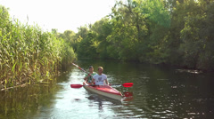 Friends go kayaking on the river sunrise among reeds Stock Footage