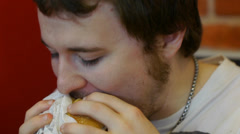Young Man Eats Double Cheeseburger - stock footage