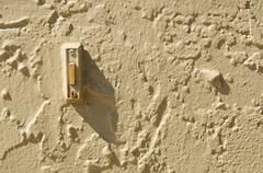 doorbell in stuccoed wall with shadow and copy space - stock photo
