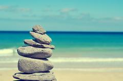 Balanced stones in a white sand beach, with a cross-processed effect Stock Photos