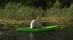 Friends go kayaking on the river among reeds and white lilies Stock Footage