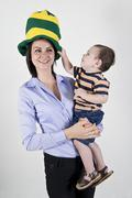 Happy mother wearing a silly hat holding her young son in her arms with a stu Stock Photos