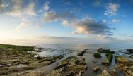 Panorama landscape looking out to sea with rocky coastline and beautful vibra Stock Photos