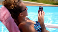 Woman Surfing Internet in the Phone while Relaxing in Pool near Hotel. HD Footage