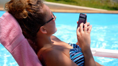 Woman Surfing Internet in the Phone while Relaxing in Pool near Hotel. Stock Footage