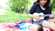 Stock Video Footage of young mother playing ukulele with little baby sleeping in the natural park