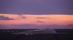 Airplane taking off at dawn with purple sky Stock Footage