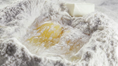 Two eggs in the middle of bleached wheat flour Stock Footage