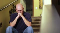 Depressed man sitting on stairs Stock Footage