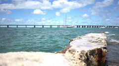 Sailboat passes by, bridge in distance Stock Footage