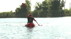 Young man goes kayaking on the river sunrise among reeds slow motion Stock Footage
