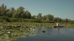Lovely girl braids hair sitting in a kayak among the reeds and lilies - stock footage