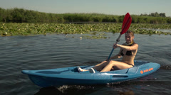 Girl go kayaking on the river among reeds and white lilies slow motion Stock Footage