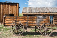 Old wooden wagon and aged log cabins Stock Photos