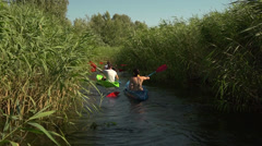 Friends go kayaking on the picturesque narrow river channel among reeds Stock Footage