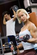 Strong beautiful woman lifting heavy dumbbells Stock Photos
