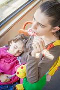 Mother holding sleeping toddler eating lollipop Stock Photos