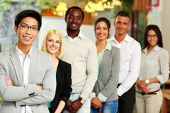 portrait of a smiling asian businessman standing in front of colleagues - stock photo