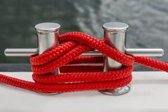 red rope fasten on stake of yacht - stock photo