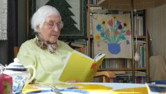 Senior Citizen reading in her living room, hand held wide shot Stock Footage
