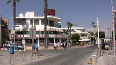 Busy road junction in Paphos with pedestrians and local bus passing Stock Footage